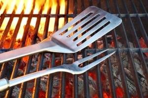 Grillrost mit Feuer und Grillbesteck